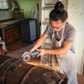 IdentityX Ambassador Trang Luu works on a horizontal cookstove for her internship in South Africa