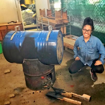 IdentityX Ambassador Trang Luu poses with a horizontal cookstove in South Africa