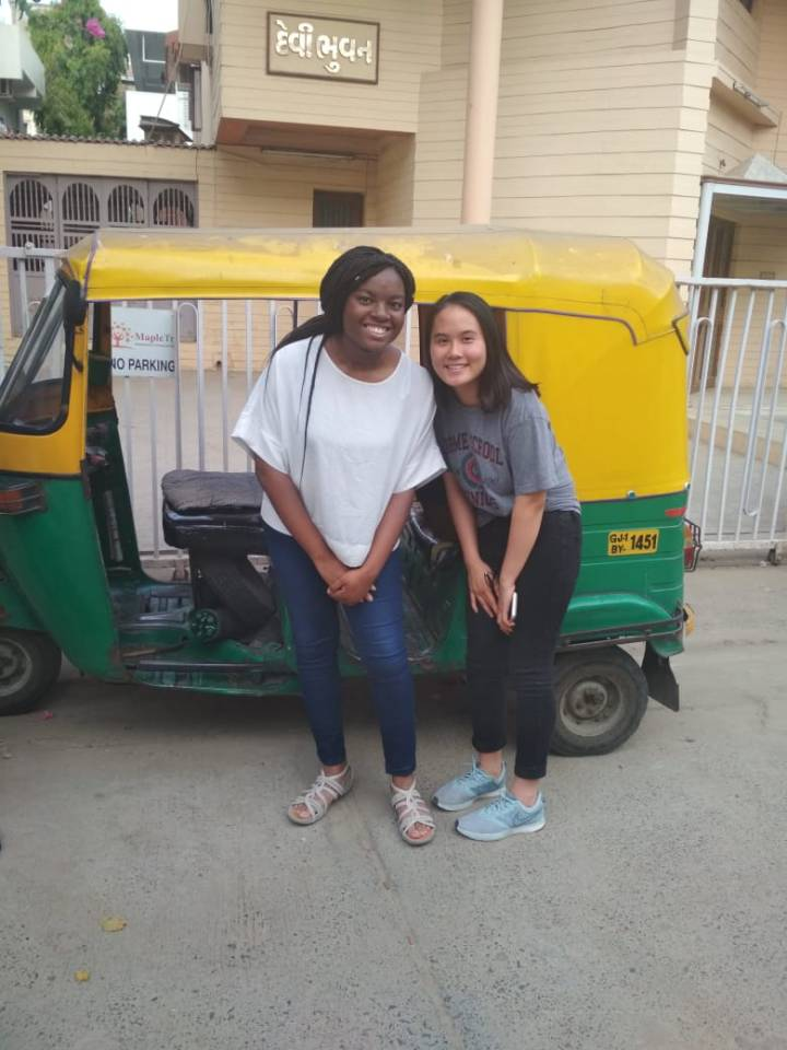 Mai and Stacy posing in front of a rickshaw in India